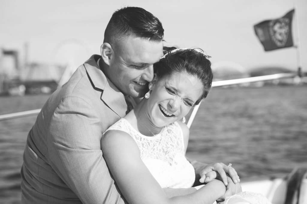 Bride and groom sit in front of boat together in black and white