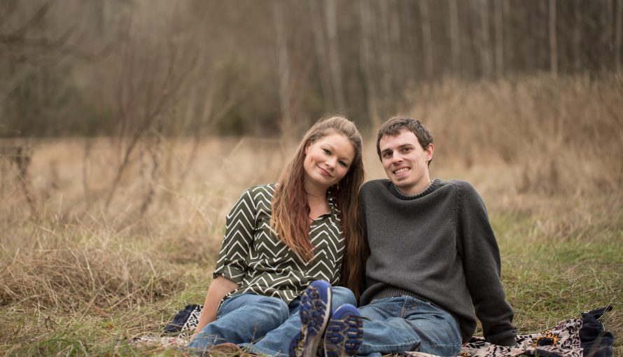 Engaged couple sits on blanket in straw field in Fort Steilacoom park