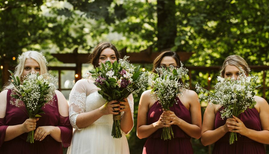Bride and three bridesmaids stand in forest with bridal bouquets in front of their faces.