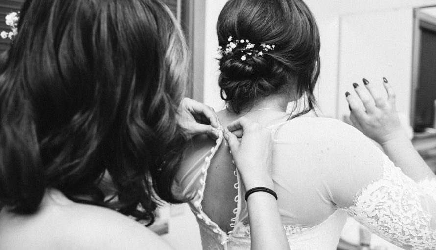 Bridesmaid helps to button pearl buttons on the back of a bride's dress