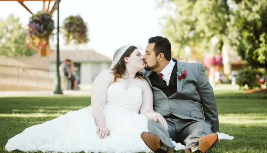 Bride and groom sit together on park grass and kiss