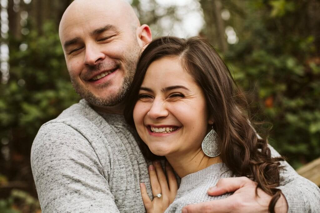 Man holds woman in his arms as they laugh together.