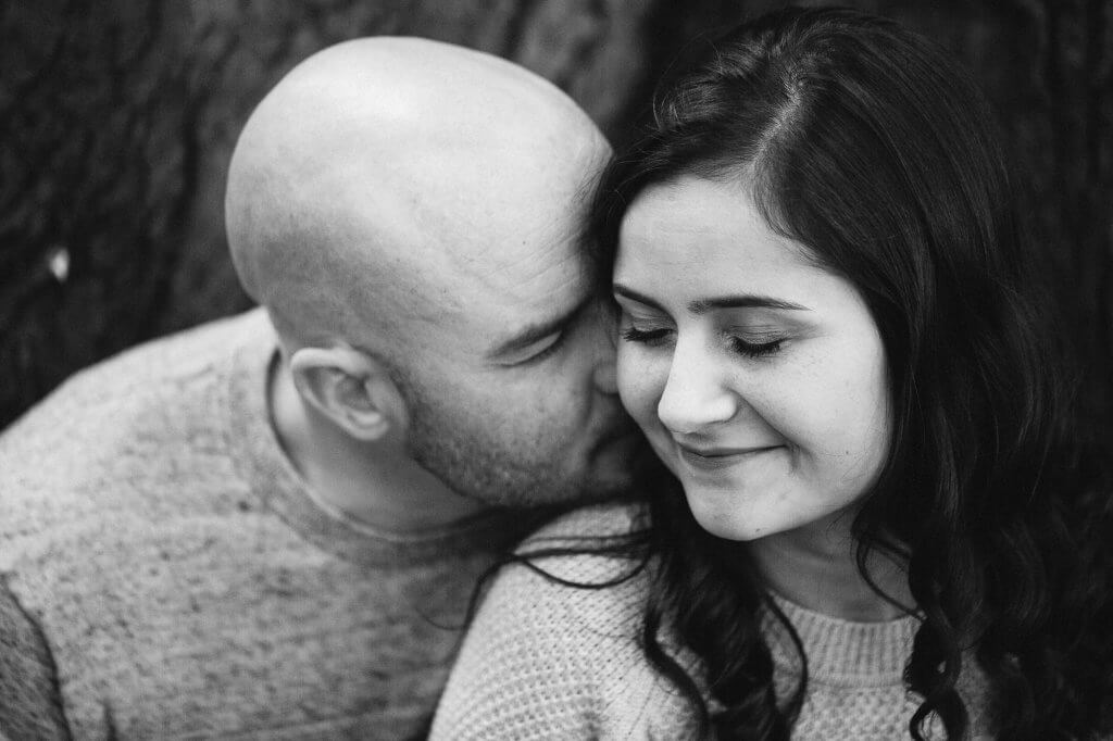 Man leans in to kiss fiance's cheek. Picture in black and white.