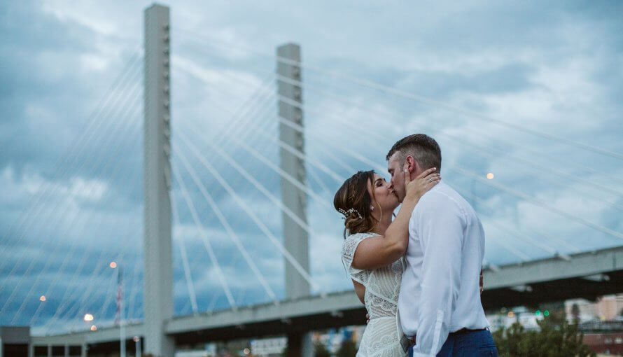 Bride and Groom kiss in front of Tacoma bridge during blue hour