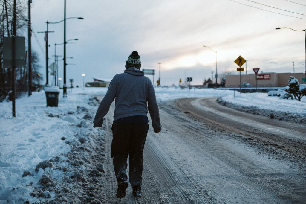 Man walks along an icy road with deep snow along the edges