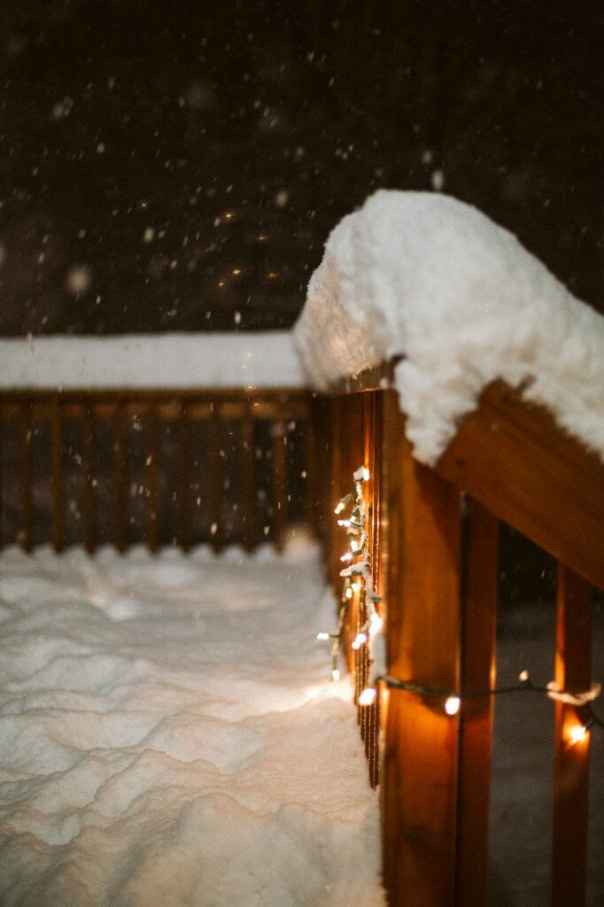 Deep snow threatens to fall off the railing of a porch with Christmas lights