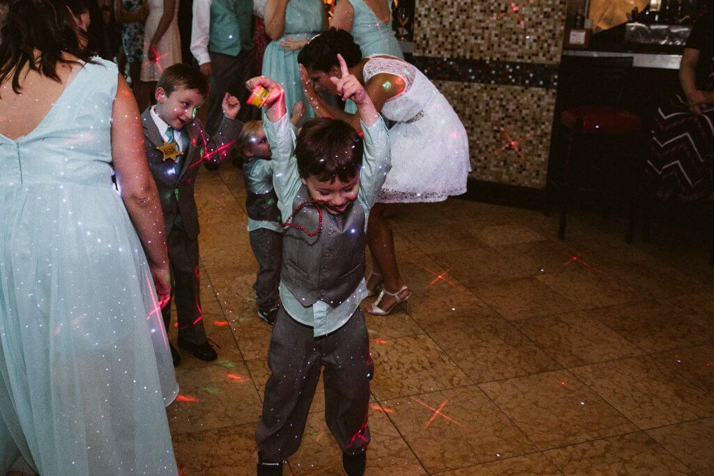 little boy in a suit dances to music at a wedding reception with lots of laser lights