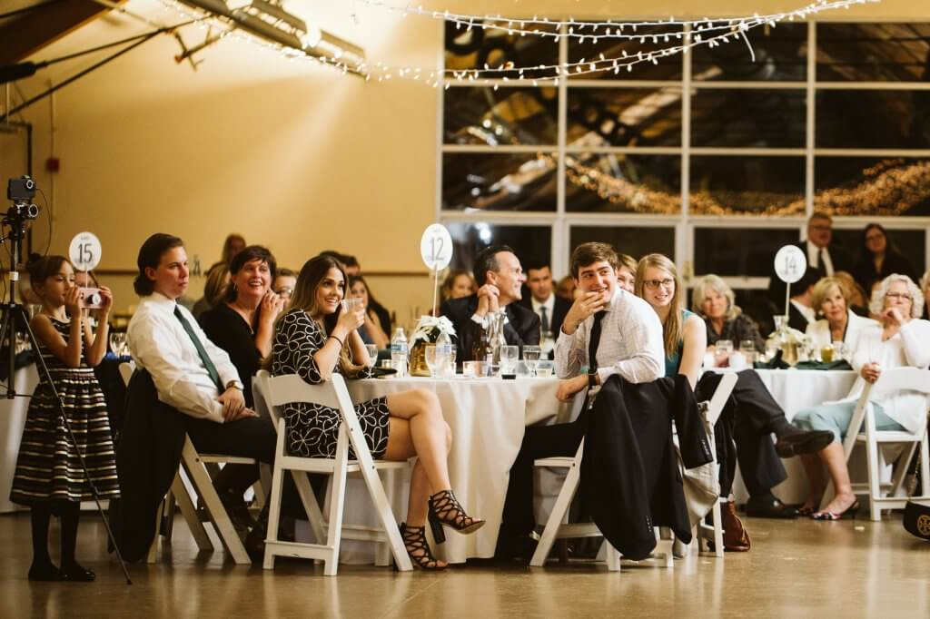 Guests at a wedding sit at tables while listening to toasts