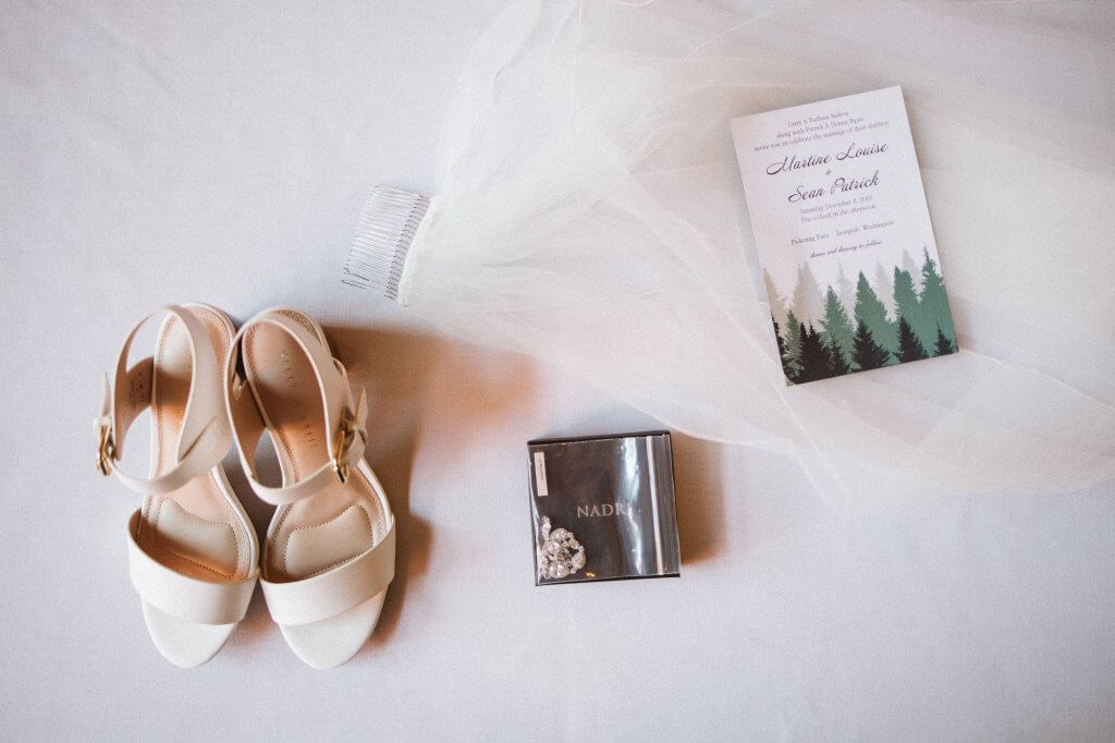 Layflat of bride's shoes, veil, program, and necklace
